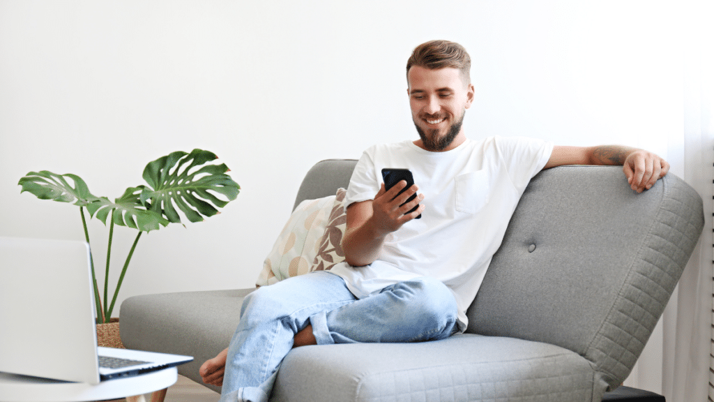 man sitting on couch at home smiling at mobile device