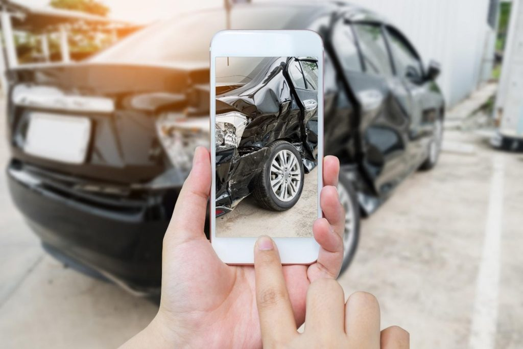 Person takes photo of car accident to submit a claim with insurance mobile app feature.