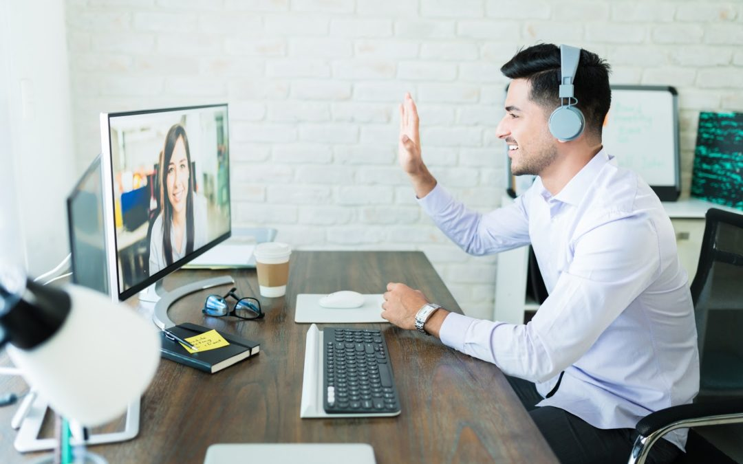 Male insurance agent wearing headphones in front of computer cross-selling insurance to customer over a video call.